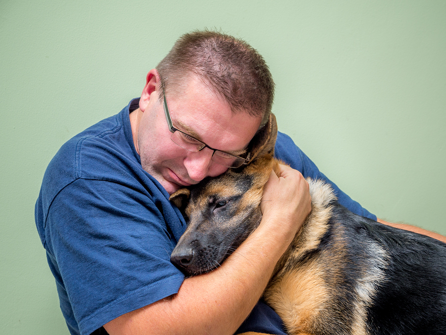 Young man hugging and consolating his dog