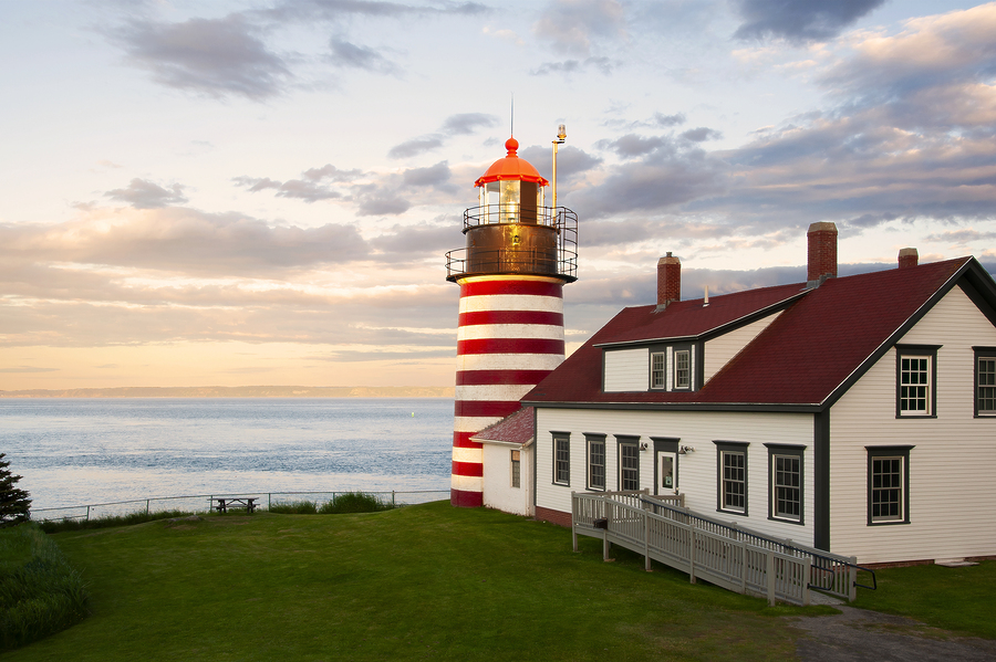 "Sunset by West Quoddy Head lighthouse, with its red and white stripes, referred to as the ""candy cane"" lighthouse, in down east Maine, in New England. The beacon is located in the easternmost point in America."